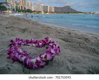 Pink and white orchid heart lei in front of the Pacific Ocean and Diamond Head in Waikiki Beach on Oahu, Hawaii.