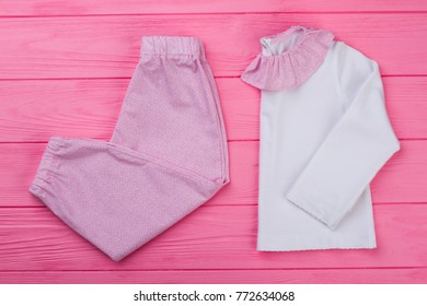Pink and white pajama set on wooden background. T-shirt with ruffle collar  and 2700b3ed3
