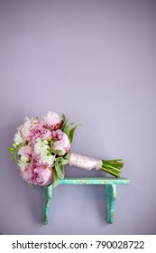 pink and white peonies bouquet on a rustic green shelf with a purple wall