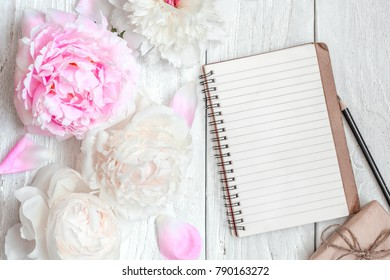 pink and white peony flowers with blank lined notebook and gift box on white wooden table. mock up. top view with copy space. valentines or women day background