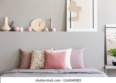 Pink and white pillows on grey bed in pastel bedroom interior with poster on bedhead. Real photo