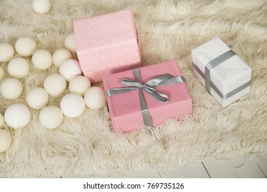 Pink and white presents on white fur carpet. Colorful gift boxes on the white fur. Merry Christmas or Happy New Year. Happy Birthday