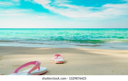 5e2a4fc47 Pink and white sandals on sand beach. Casual style flip-flop were removed at