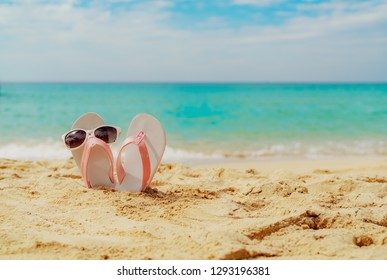 Pink and white sandals, sunglasses on sand beach at seaside. Casual fashion style flipflop and glasses. Summer vacation on tropical beach. Fun holiday travel on sandy beach. Summertime. Summer vibes.