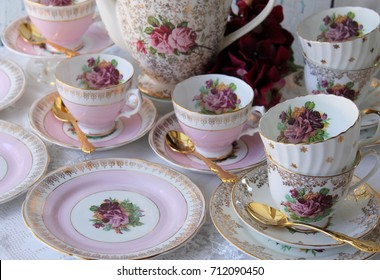 Pink and white vintage teacups and saucer with purple roses and gold stars, gold cutlery flatware, high tea party