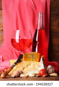 Pink wine and different kinds of cheese on fabric background