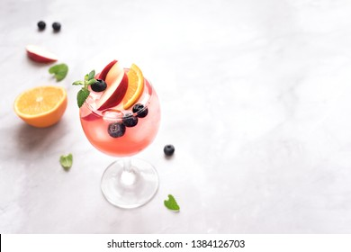 Pink Wine Sangria drink with Fruits and Blueberries on white marble, copy space. Glass of cold summer iced pink sangria cocktail.