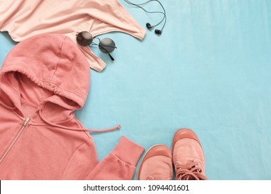 Pink woman hoody, top, sneakers, round sunglasses and headphones on blue background. Casual street style, top view point, flat lay.