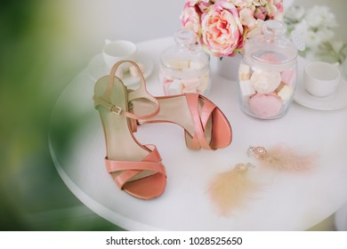 Pink women shoes, a bouquet of spring flowers and marshmallows on white background.  Morning of the bride. Concept of holiday, birthday, Easter, March 8.  flat lay