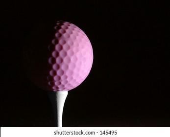 Pink womens golf ball on tee