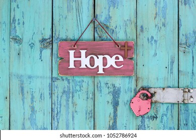 Pink wood sign with the word Hope and a religious cross next to heart lock hanging on rustic antique teal blue wooden door; Easter and Memorial Day holiday concept background with copy space