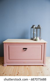 Pink wooden chest on a blue wall background