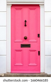 Pink wooden front door with white frame and black letterbox, lock and handle