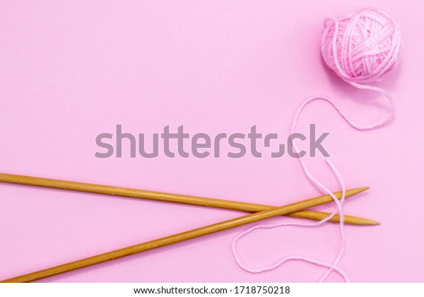 Pink wool and wooden knitting needles on a pink background with room for copy.