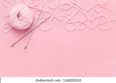 Pink yarn skein, knitting needles and border of ornate thread on pink copy space. Top view, needlework concept.