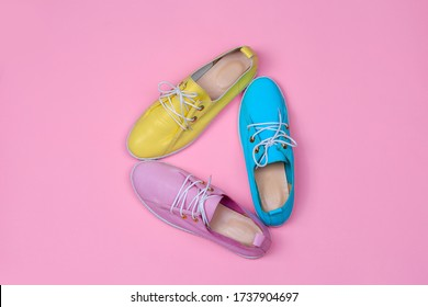 Pink, yellow, and blue shoes. Bright colorful foorwear design concept. Top view flat lay composition on pink background.
