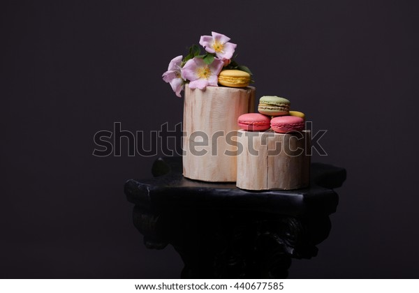 Pink yellow and green macaron on wooden stump with soft spring flowers and leaves on grey background, copy space