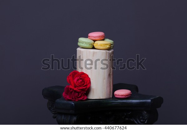 Pink yellow and green macaron on wooden stump with soft rose flowers on grey background, copy space