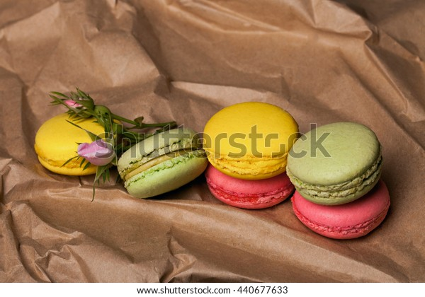 Pink yellow and green macaron on brown paper with soft spring flowers on grey background