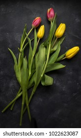 Pink and yellow tulips on a dark, grungy background.
