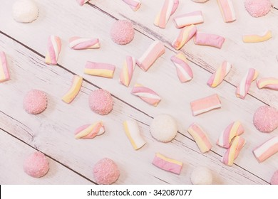 Pink, yellow and white marshmallows scattered on off white wooden background in warm tones