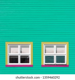 Pink yellow and white windows on a green wooden wall. Square, minimalism style of the houses of Iles de la Magdalen, Canada, in bright colours with space for text.