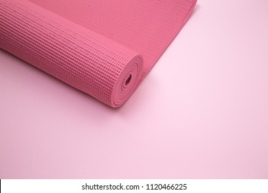 pink yoga or pilates mat on pink background. equipment for healthy lifestyle and diet. rolled up. preparing for exercise. high angle view.