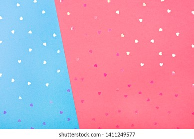 Pink-blue background-substrate, with heart-sparkles glitter scattered on it. Top view, flat lay