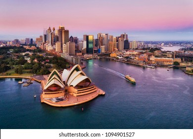 Pinkish colourful sunrise over Sydney city CBD on waterfront of Harbour around Circular quay with major architectural landmarks and symbols of Australia.