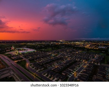 Pinks and blues across sunset sky Aerial view above suburb neighborhood real estate market new city living in Suburbia community north of Austin , Texas During amazing dusk city lights