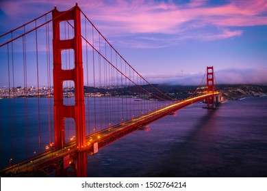 Pinks clouds at sunset and long exposure light trails across Golden Gate Bridge Spectacular view of San Francisco , California , USA as the Fog slowly rolls in off the Pacific coast