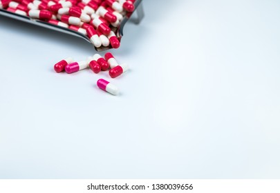 Pink-white and red-white capsule on white table and blurred stainless steel drug tray. Love pills for Valentine's day concept. Pharmaceutical industry. Antibiotic capsule pills. Outstanding pills.