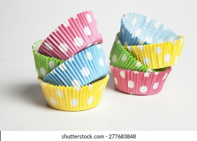 Pink,yellow,blue and green cupcake liners in white background