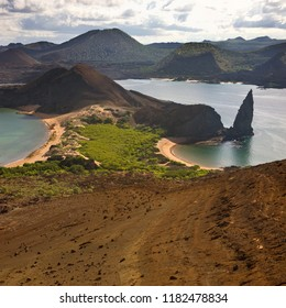 Pinnacle Rock and the volcanic landscape of cinder cones and lava on the island of Bartolome in the Galapagos Islands, Ecuador.