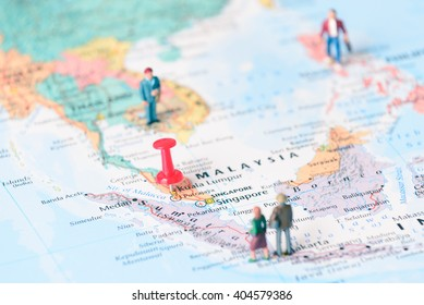 Pinned on map of Kuala Lumpur in Malaysia and miniature travelers.