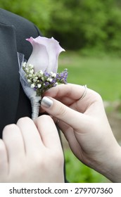 Pinning on a boutonniere for a prom date.
