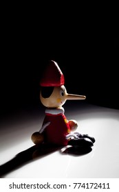 Pinocchio doll on a black background with shadow and dramatic light