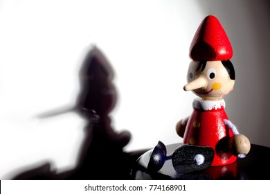 Pinocchio doll on a gray background with shadow and dramatic light