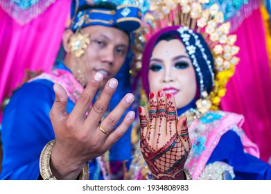 Pinrang, Indonesia - a bride and groom showing a wedding ring in a Bugis-Makassar traditional bandage in Batulappa, Pinrang Indonesia - on July 9, 2017