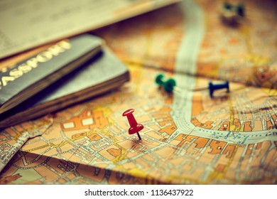 pins marking travel itinerary points on map and passport