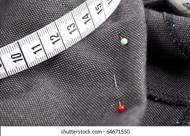 Pins and measuring tape on fabric, ready for sewing.