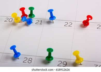 Pins on a clean calendar. Event planning