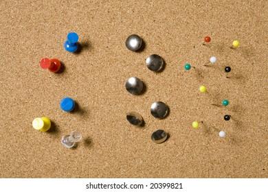 Pins and tacks on a cork board