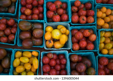Pint baskets of organic red tomatoes on the counter. Fresh organic produce on sale at the local farmers market. Organic, agriculture products. Freshly, seasonal harvested vegetables. Bio, healthy.