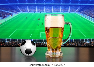 Pint of beer and ball before tv showing soccer