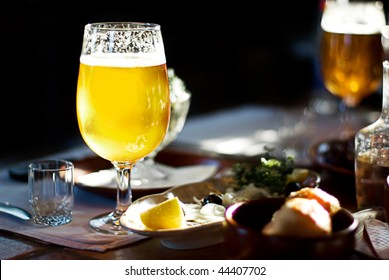 A Pint of Beer on a  table and food background
