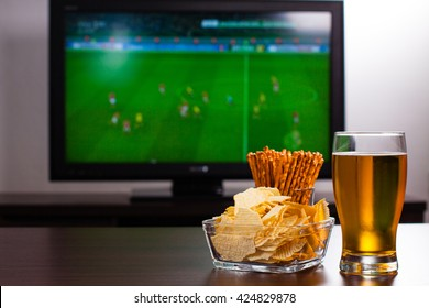 Pint of beer on the table in front of television show off football.