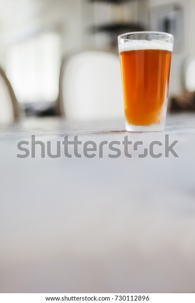 Pint of beer sitting on a grey table