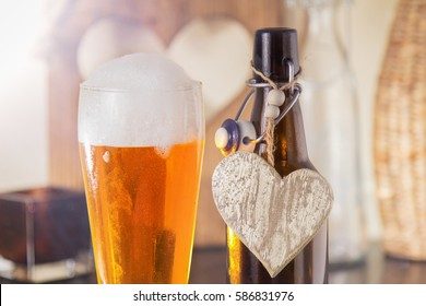 Pint of chilled golden beer in a glass with a good frothy head alongside the empty beer bottle with a heart on it either conceptual of I Love Beer or of a special Valentine drink for a loved one