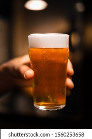 A pint of cold beer being held